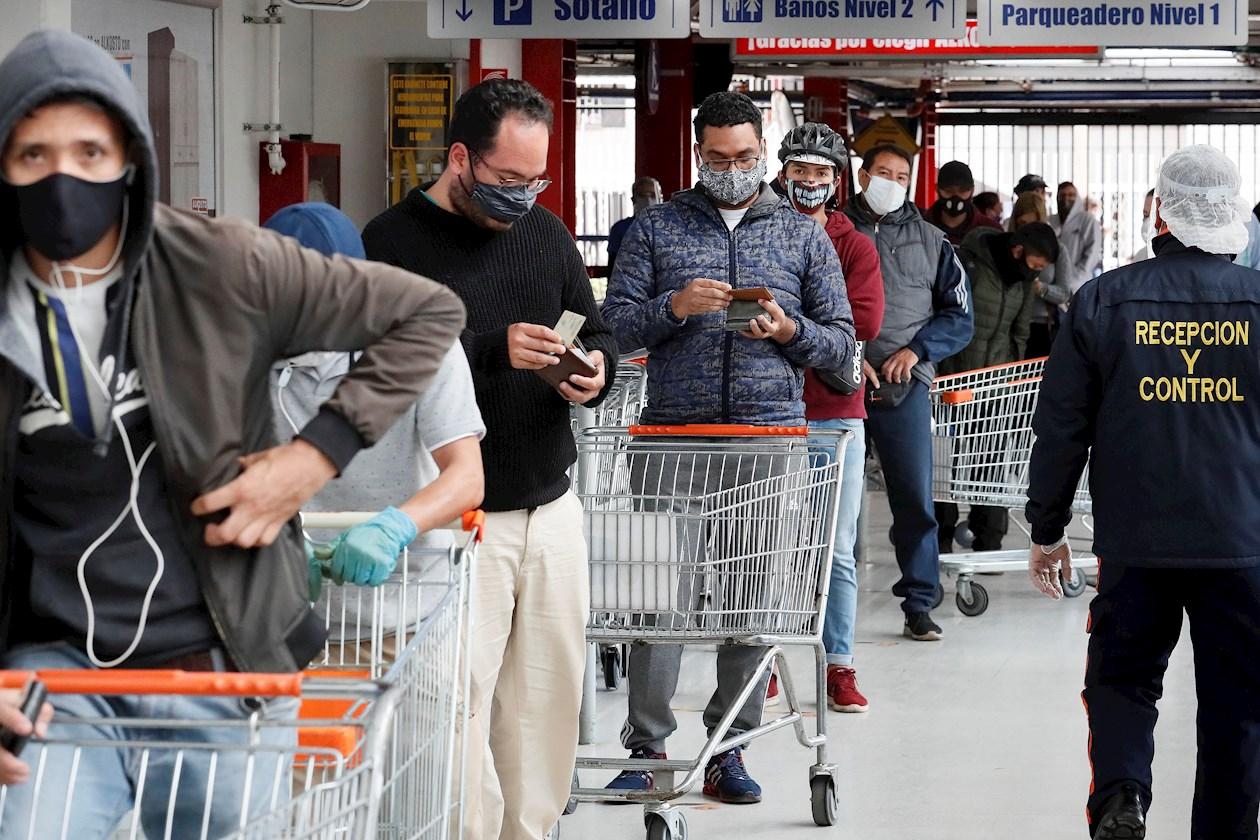 Una fila de compradores fue registrada este viernes antes de ingresar a un almacén en Bogotá (Colombia).