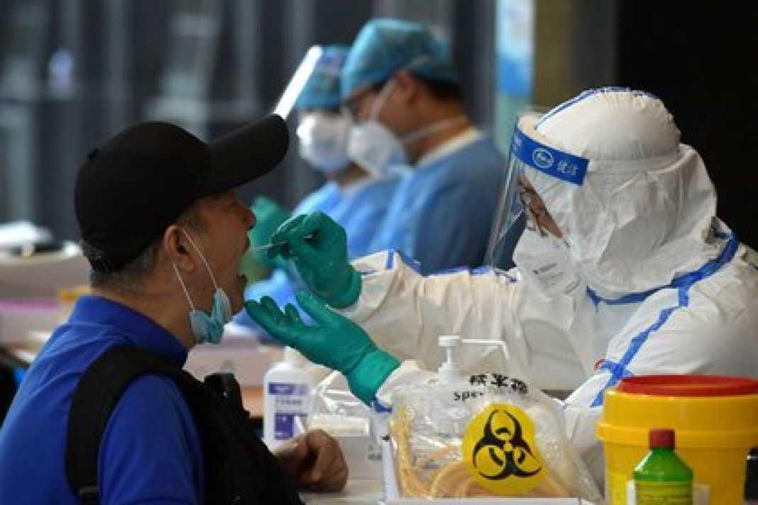 Un personal médico con traje de protección recoge hisopos de personas que han viajado recientemente a Pekín para realizar pruebas de ácido nucleico, tras los nuevos casos de infecciones de la enfermedad coronavirus (COVID-19) en la capital china, en Nanjing, provincia de Jiangsu, China, el 15 de junio de 2020. China Daily vía REUTERS