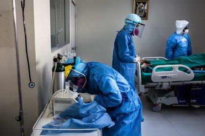Trabajadores de la salud atienden a un paciente contagiado con coronavirus en Lima (Perú). EFE/Sergi Rugrand/Archivo