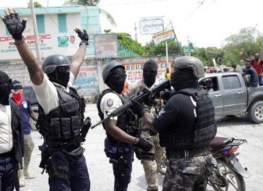"""Manifestantes con uniformes de policía levantan sus brazos mientras se enfrentan a un oficial de la Policía Nacional Haitiana (PNH) de turno que sostiene un rifle durante una protesta organizada por el grupo radical """"Fantom 509"""" en las calles de Puerto Príncipe, Haití, el 14 de septiembre de 2020. (REUTERS/Andrés Martínez Casares)"""