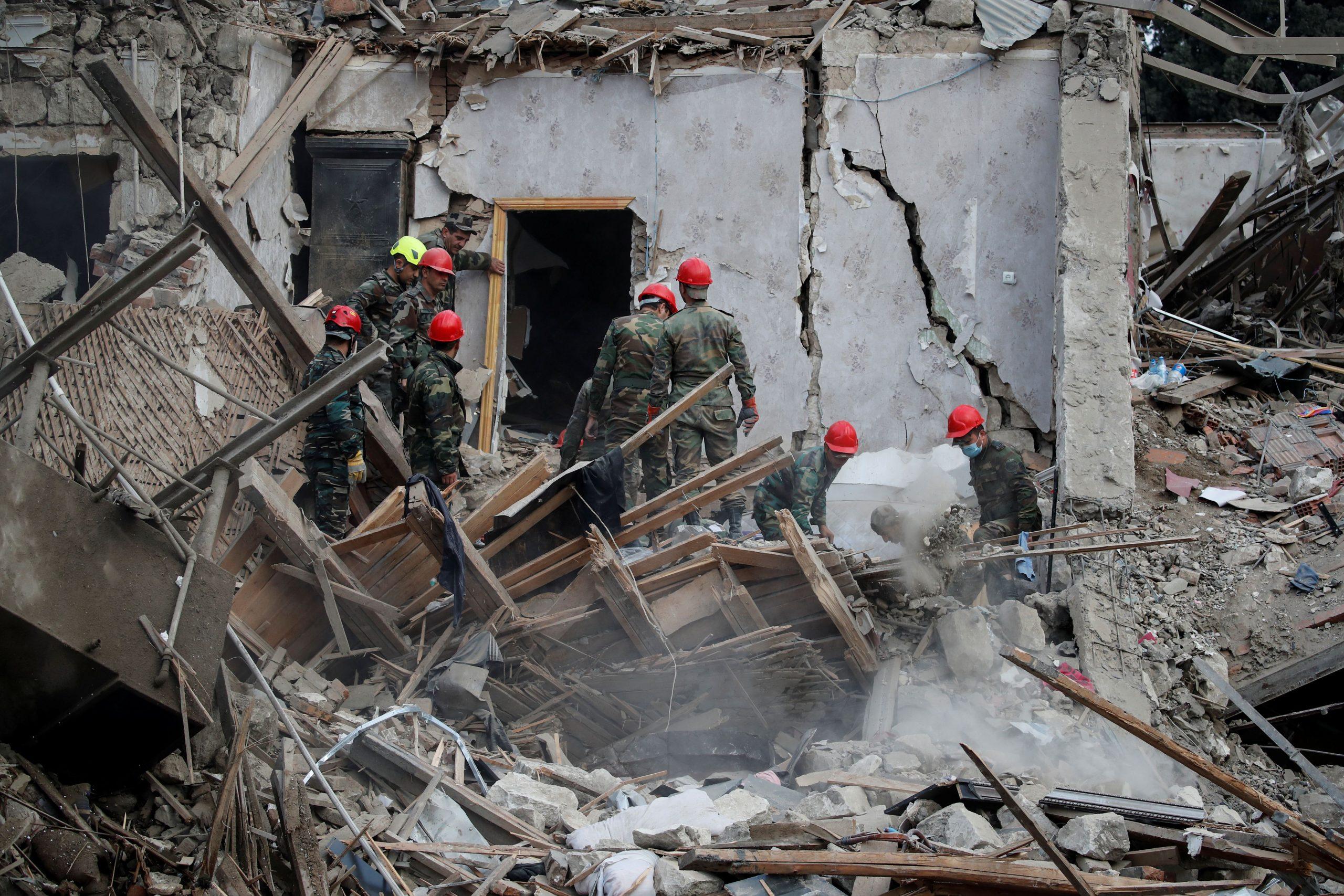Equipos de búsqueda y rescate trabajan en el lugar de la explosión alcanzado por un cohete durante los combates en la región separatista de Nagorno-Karabaj en la ciudad de Ganja, Azerbaiyán. REUTERS/Umit Bektas
