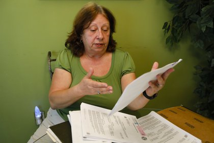 Maria Aurora Estevez, de 64 años, revisa sus documentos legales en Miami (AFP)