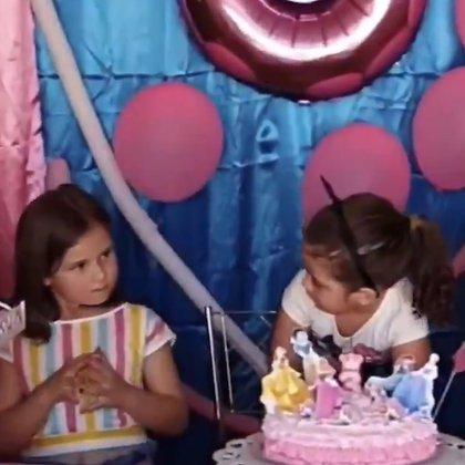 Maria Eduarda mira sorprendida a Maria Antonia después de que esta le apaga las velas de su cumpleaños.