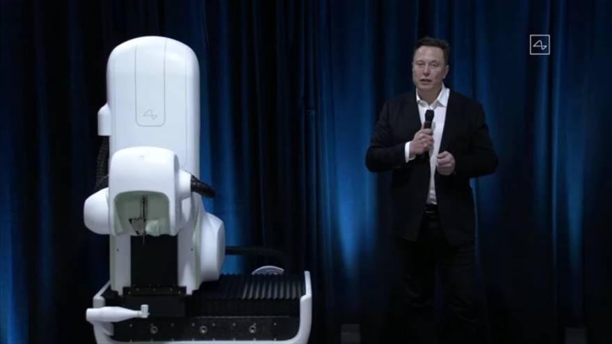 Elon Musk junto al robot que se utilizaría en las cirugías para insertar los chips en el cerebro