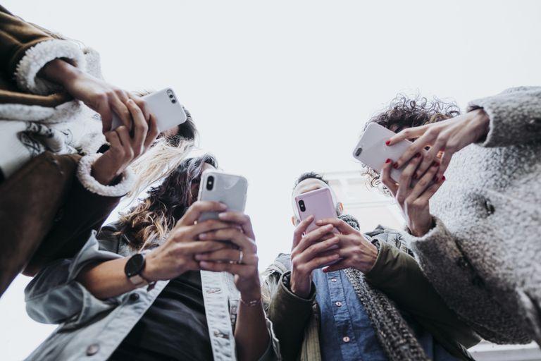 Cuatro amigos usan sus teléfonos móviles en la calle.