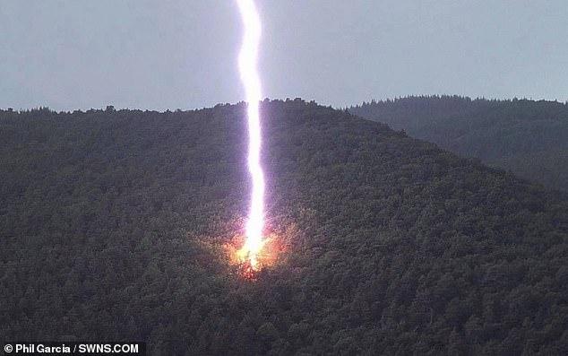 Esta increíble imagen captura un rayo gigantesco cuando golpea la ladera de una montaña.  La foto salvaje fue tomada en junio pasado por Phil García, mientras caminaba con sus amigos en Pecos, Nuevo México.
