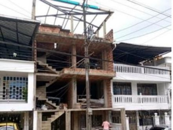 En Buenaventura, un hombre construye un edificio de 4 pisos y tiene que mover un poste eléctrico